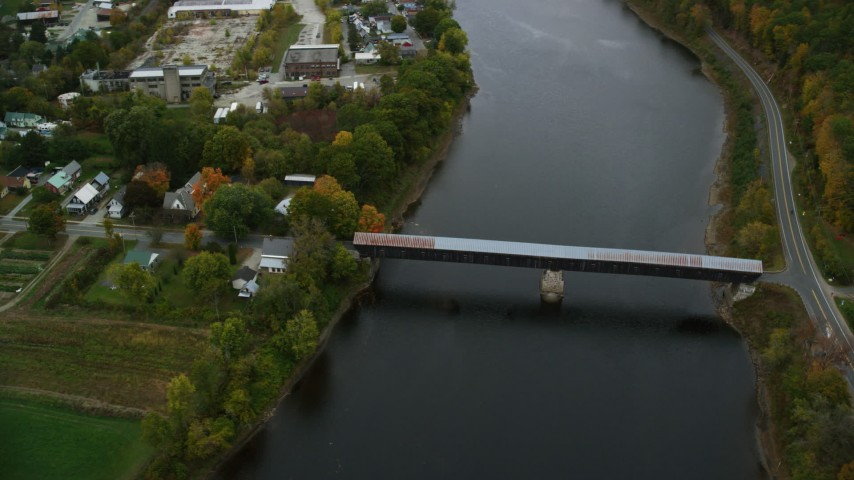 6K stock footage aerial video orbiting covered bridge, Connecticut River, neighborhood, autumn, Windsor, Vermont Aerial Stock Footage | AX151_060