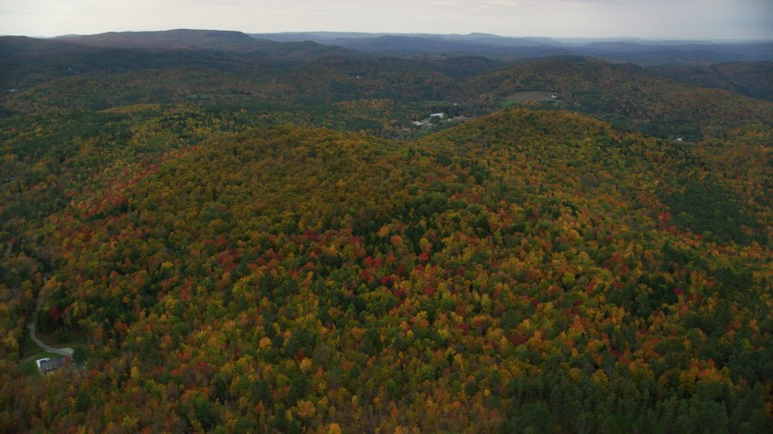 6K stock footage aerial video flying by brightly colored forested hills, autumn, overcast, Cornish, New Hampshire Aerial Stock Footage | AX151_067