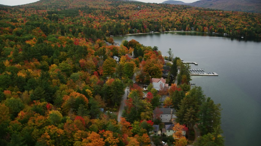 6K stock footage aerial video orbiting colorful forest, waterfront homes, Lake Sunapee, autumn, Newbury, New Hampshire Aerial Stock Footage | AX151_088