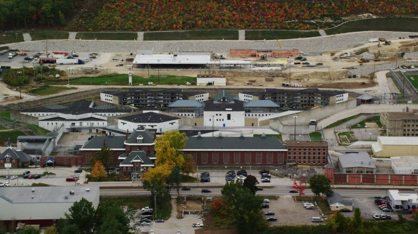 6K stock footage aerial video orbiting New Hampshire State Prison, baseball diamond, light traffic passing by, autumn, Concord, New Hampshire Aerial Stock Footage | AX151_176