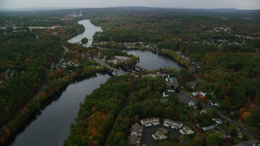 6K stock footage aerial video orbiting small bridges, Merrimack River, small town, autumn, Hooksett, New Hampshire Aerial Stock Footage | AX152_013