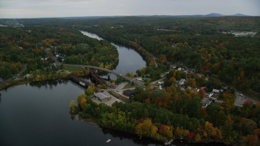 6K aerial video orbiting small town, small bridges, Merrimack River, autumn, Hooksett, New Hampshire Aerial Stock Footage | AX152_016