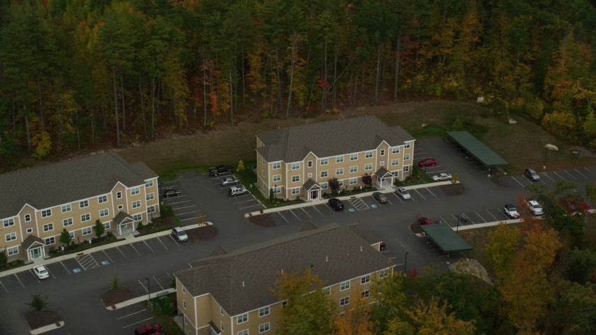 6K stock footage aerial video flying by apartment buildings, colorful trees in autumn, Hooksett, New Hampshire Aerial Stock Footage | AX152_021