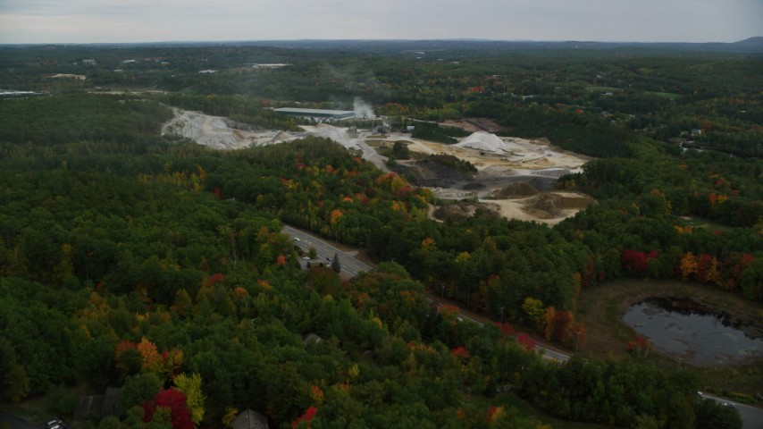 6K aerial video flying over colorful trees, approaching small quarry, autumn, Hooksett, New Hampshire Aerial Stock Footage | AX152_023