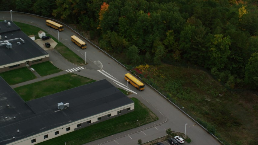 6K stock footage aerial video orbiting Hooksett Memorial School, tracking buses leaving, autumn, Hooksett, New Hampshire Aerial Stock Footage | AX152_028