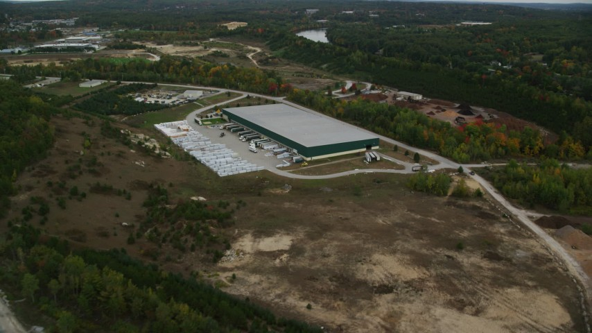 6K aerial video over quarry, approach warehouse building, autumn, Hooksett, New Hampshire Aerial Stock Footage | AX152_029