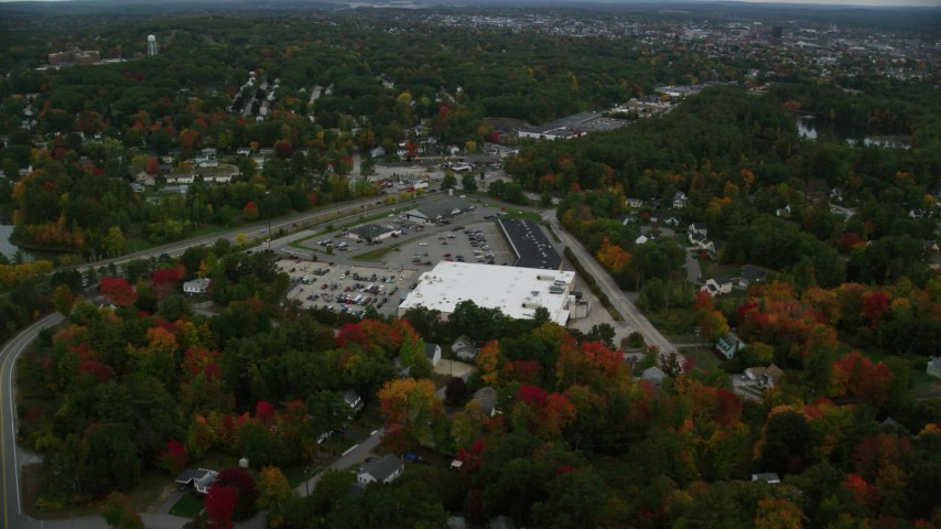 6K stock footage aerial video flying over colorful foliage, approaching a store, tilt down, autumn, Manchester, New Hampshire Aerial Stock Footage | AX152_035