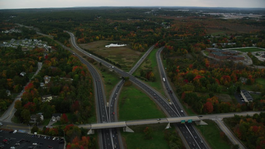 6K stock footage aerial video flying over Interstate 93, Interstate 293 interchange, autumn, overcast, Manchester, New Hampshire Aerial Stock Footage | AX152_047
