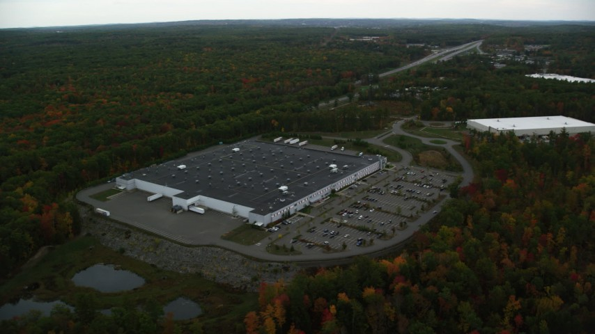 6K stock footage aerial video flying by warehouse building, forest in autumn, Londonderry, New Hampshire Aerial Stock Footage AX152_051 | Axiom Images