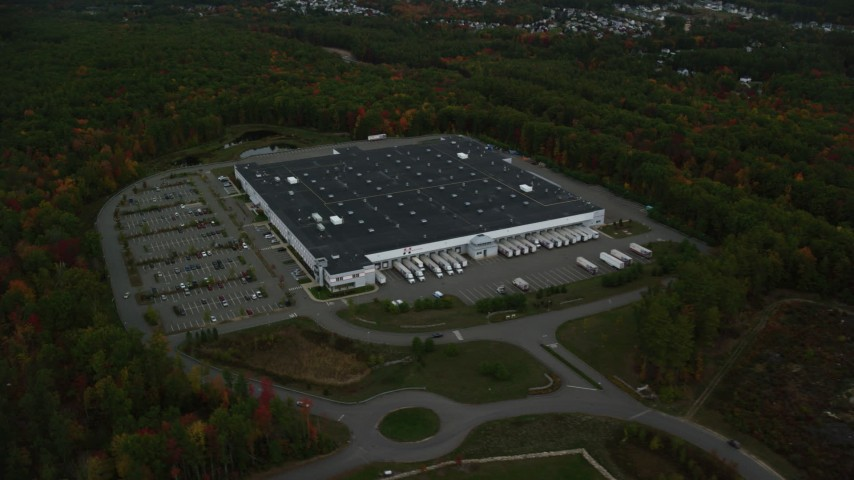 6K stock footage aerial video flying away from a warehouse building, dense forest, autumn, Londonderry, New Hampshire Aerial Stock Footage | AX152_052