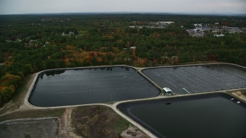 6K stock footage aerial video flying by water treatment plant ponds, colorful foliage, autumn, Derry, New Hampshire Aerial Stock Footage | AX152_062
