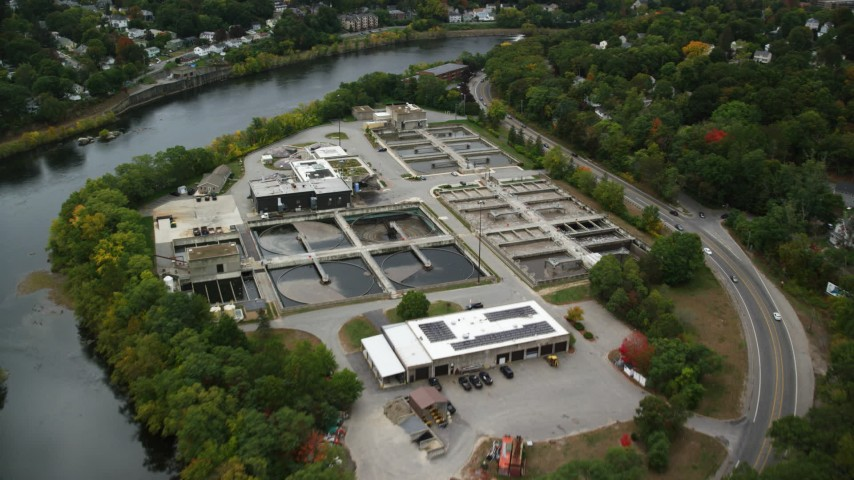 6K stock footage aerial video flying over water treatment plant along a river, autumn, Lowell, Massachusetts Aerial Stock Footage | AX152_126