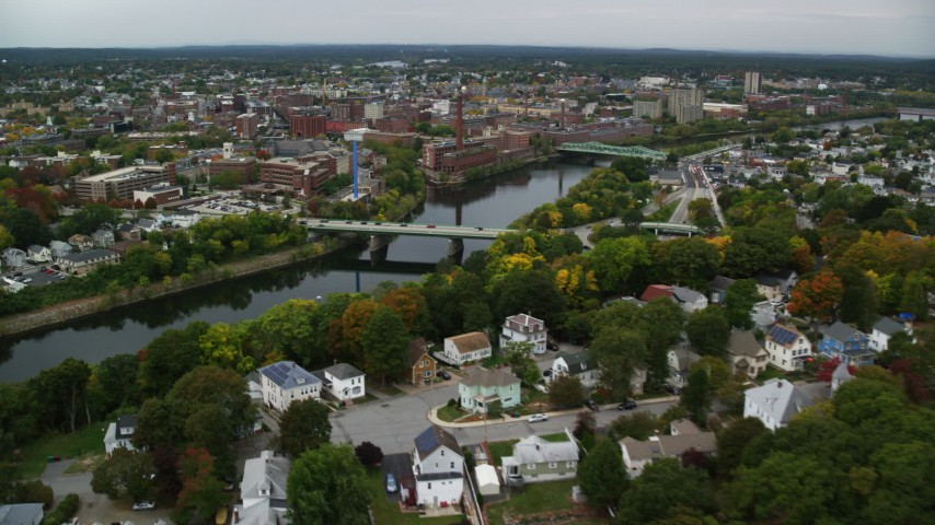 6K stock footage aerial video flying over town toward bridge spanning a river, approaching a hospital, Lowell, Massachusetts Aerial Stock Footage | AX152_127