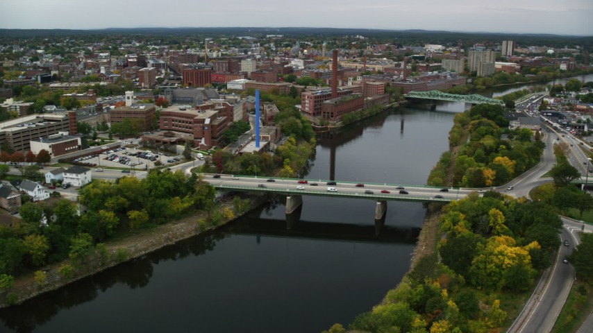6K stock footage aerial video flying over bridge on a river toward abandoned factory, autumn, Lowell, Massachusetts Aerial Stock Footage | AX152_128