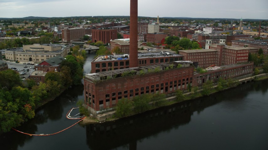 6K stock footage aerial video flying by riverside abandoned factory and smoke stack, autumn, Lowell, Massachusetts Aerial Stock Footage | AX152_129