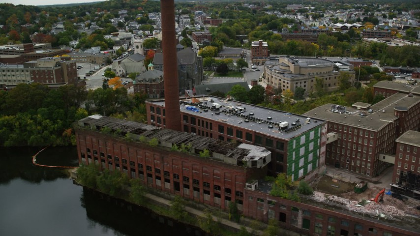 6K stock footage aerial video tilting down on abandoned factory and smoke stack, Lowell, Massachusetts Aerial Stock Footage | AX152_130