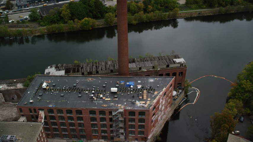 6K stock footage aerial video orbiting away from an abandoned factory and smoke stack along the river, autumn, Lowell, Massachusetts Aerial Stock Footage | AX152_131