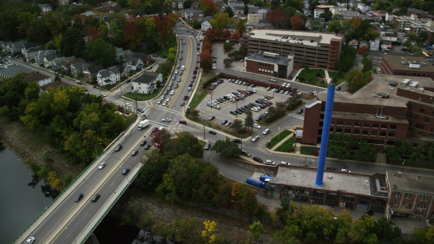 6K stock footage aerial video orbiting Saints Medical Center and a blue smoke stack, near the river, autumn, Lowell, Massachusetts Aerial Stock Footage | AX152_132