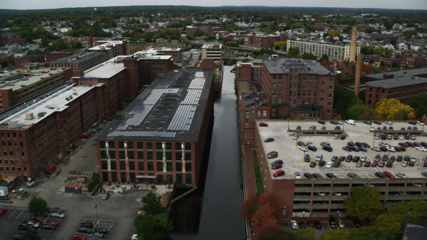 6K stock footage aerial video following a canal lined with factory buildings, autumn, Lowell, Massachusetts Aerial Stock Footage | AX152_135