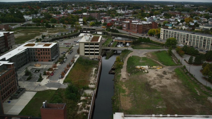 6K stock footage aerial video flying over canal toward locks and dam, autumn, Lowell, Massachusetts Aerial Stock Footage | AX152_136