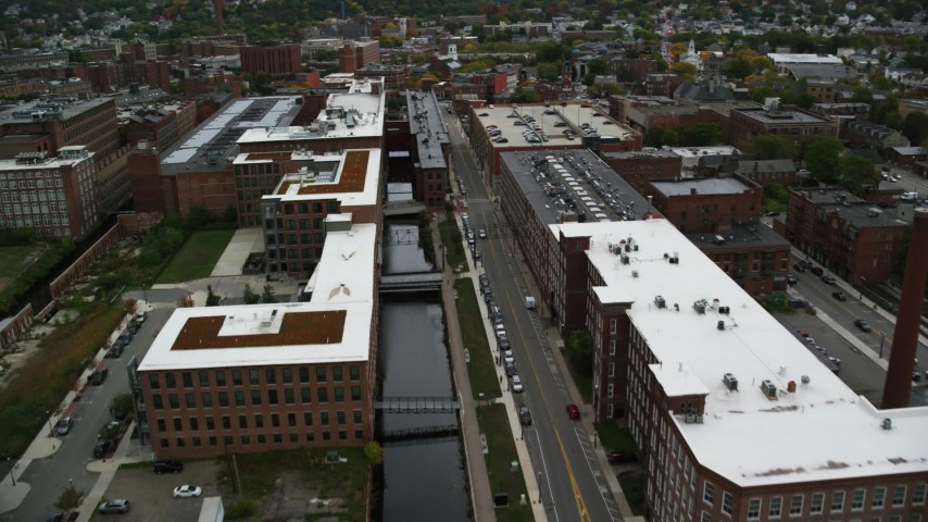 6K stock footage aerial video flying over factory buildings along a canal, autumn, Lowell, Massachusetts Aerial Stock Footage | AX152_137