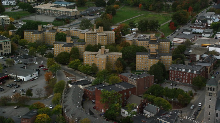 6K stock footage aerial video flying by urban apartment buildings among partial fall foliage, Lowell, Massachusetts Aerial Stock Footage | AX152_139