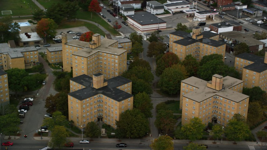 6K stock footage aerial video orbiting urban apartment buildings and changing color trees, autumn, Lowell, Massachusetts Aerial Stock Footage | AX152_140