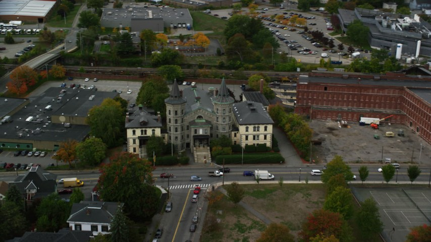 6K stock footage aerial video flying by a condominium complex and busy street, autumn, Lowell, Massachusetts Aerial Stock Footage | AX152_141