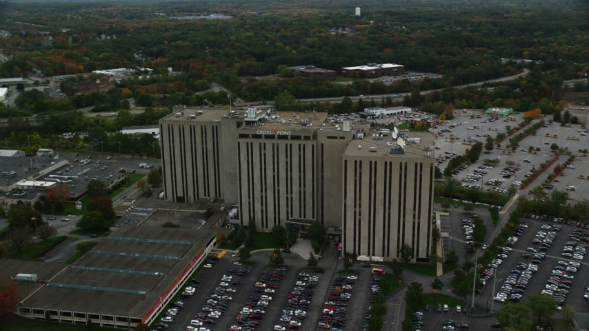 6K stock footage aerial video orbiting away from an office building and parking lots, autumn, Lowell, Massachusetts Aerial Stock Footage | AX152_145