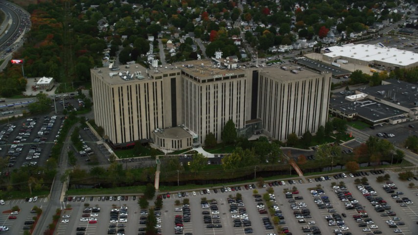 6K stock footage aerial video office building along parking lots and trees with fall foliage, Lowell, Massachusetts Aerial Stock Footage | AX152_147