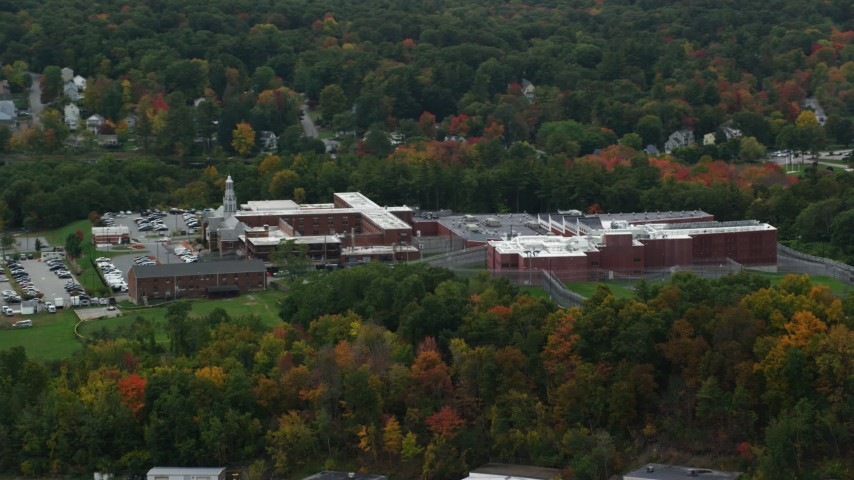 6K stock footage aerial video approaching a prison surrounded by partial fall foliage, autumn, Billerica, Massachusetts Aerial Stock Footage | AX152_152