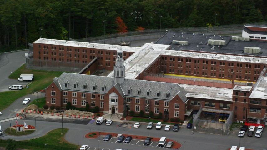 6K stock footage aerial video off a close up approach to a prison surrounded by trees, autumn, Billerica, Massachusetts Aerial Stock Footage | AX152_153