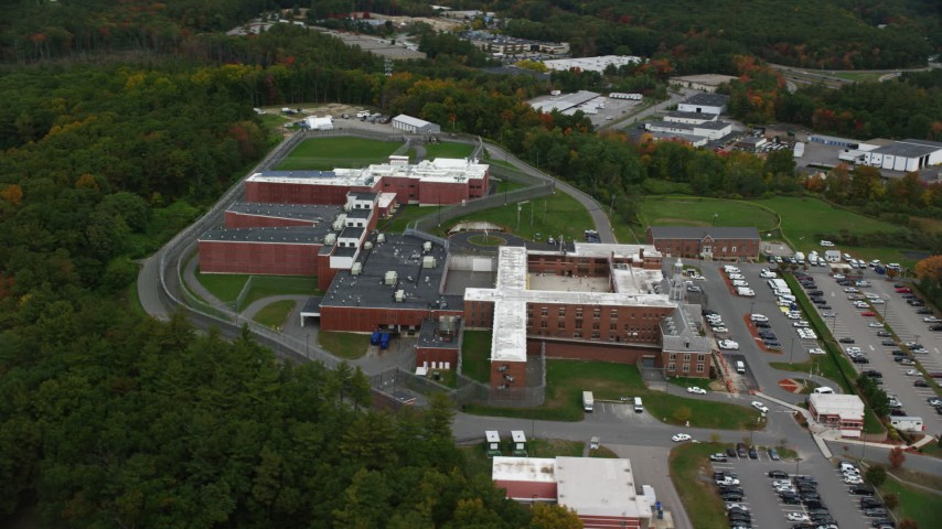 6K stock footage aerial video orbiting away from a prison and over trees with fall foliage, Billerica, Massachusetts Aerial Stock Footage | AX152_155