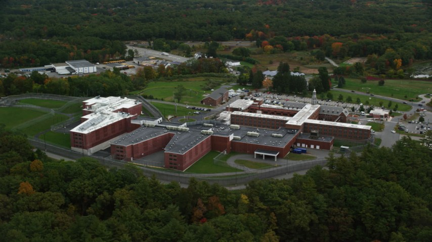 6K stock footage aerial video flying over trees and away from a prison, autumn, Billerica, Massachusetts Aerial Stock Footage   AX152_156
