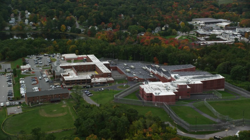 6K stock footage aerial video flying away from a prison backed by fall foliage, Billerica, Massachusetts Aerial Stock Footage | AX152_158