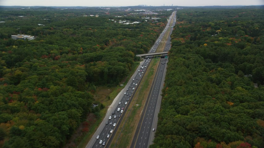 6K stock footage aerial video flying over overpass and highway among partial fall foliage, Bedford, Massachusetts Aerial Stock Footage | AX152_163