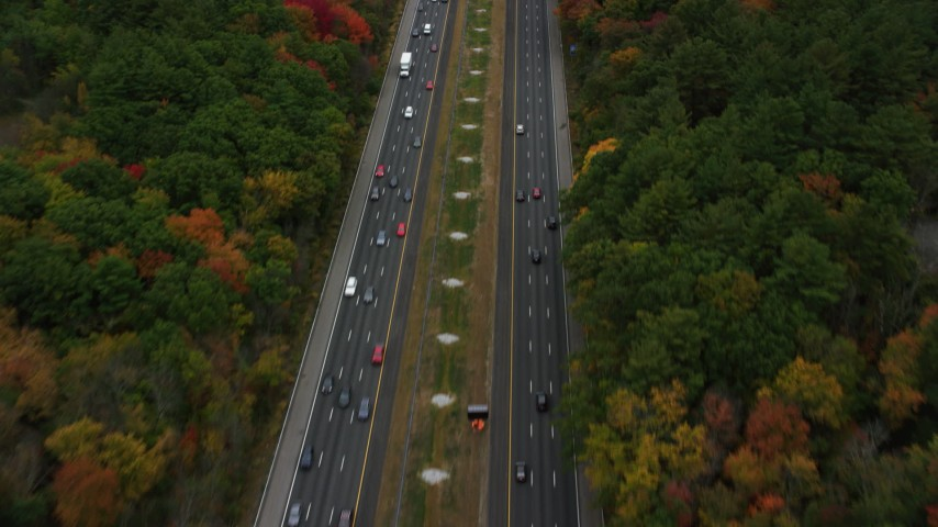 6K aerial video following a highway surrounded by fall foliage, Bedford, Massachusetts Aerial Stock Footage AX152_164