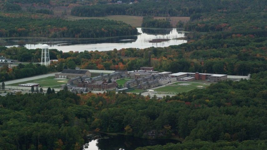 6K stock footage aerial video of a slow approach over fall foliage toward Massachusetts Correctional Institution at Norfolk, Massachusetts Aerial Stock Footage | AX152_210