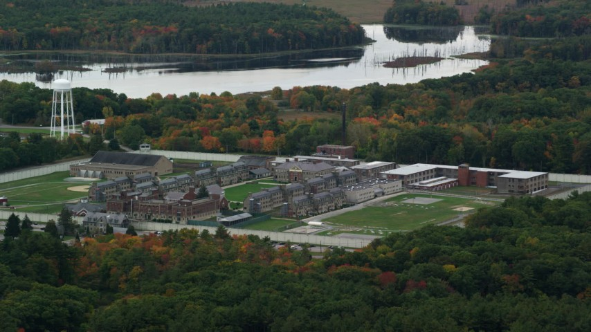 6K stock footage aerial video flying over fall foliage toward Massachusetts Correctional Institution at Norfolk and the water, Massachusetts Aerial Stock Footage | AX152_211