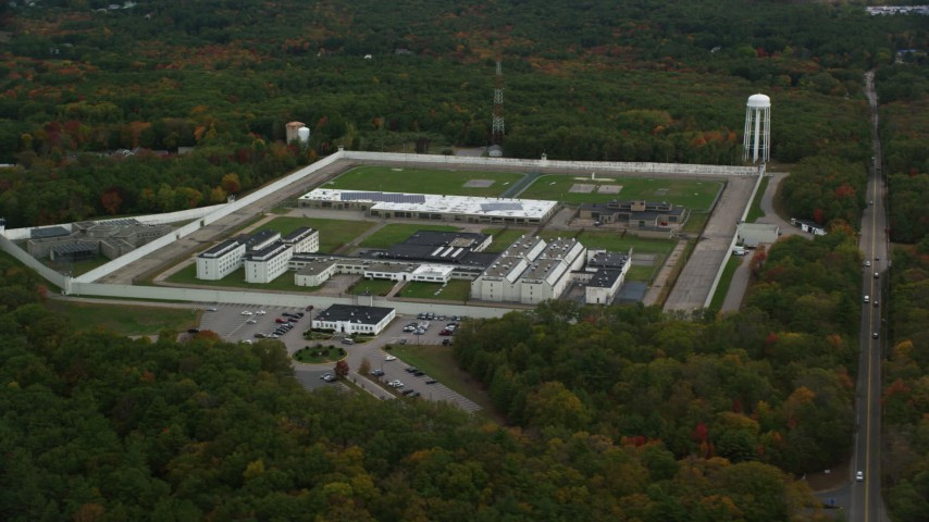 6K stock footage aerial video flying away from Massachusetts Correctional Institution Cedar Junction and fall trees, autumn, Walpole, Massachusetts Aerial Stock Footage AX152_216