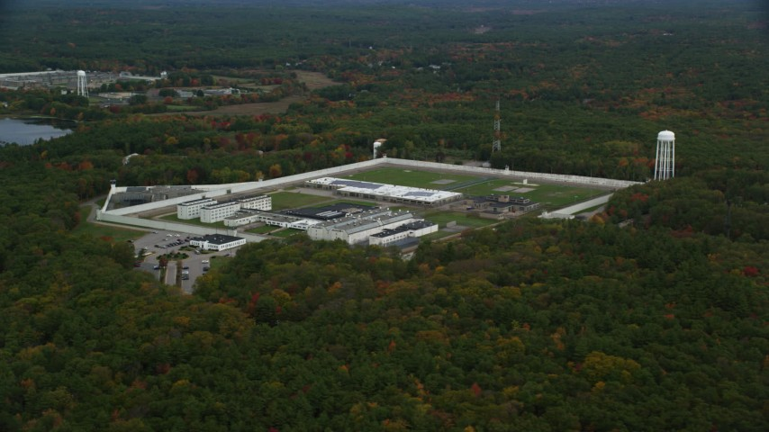 6K stock footage aerial video flying away from Massachusetts Correctional Institution Cedar Junction, over fall foliage, Walpole, Massachusetts Aerial Stock Footage | AX152_217
