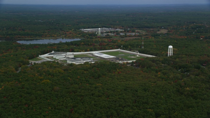 6K stock footage aerial video of a wide view of fall foliage approaching Massachusetts Correctional Institution Cedar Junction, Walpole, Massachusetts Aerial Stock Footage | AX152_218