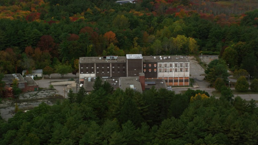 6K stock footage aerial video flying over fall foliage toward abandoned hospital, Walpole, Massachusetts Aerial Stock Footage | AX152_219