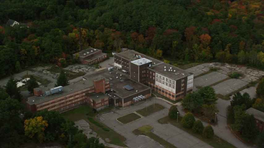 6K stock footage aerial video orbiting away from an abandoned hospital among fall foliage, Walpole, Massachusetts Aerial Stock Footage | AX152_220