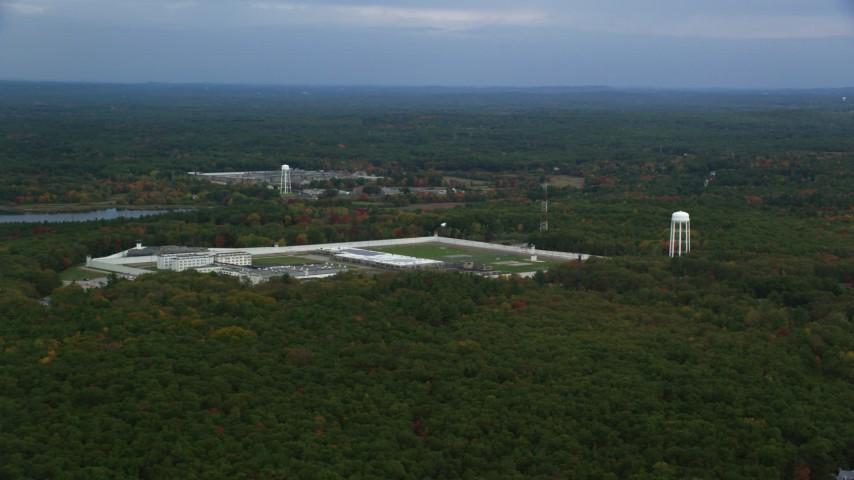 6K stock footage aerial video flying over trees with fall foliage along the Massachusetts Correctional Institution Cedar Junction, Walpole, Massachusetts Aerial Stock Footage | AX152_222