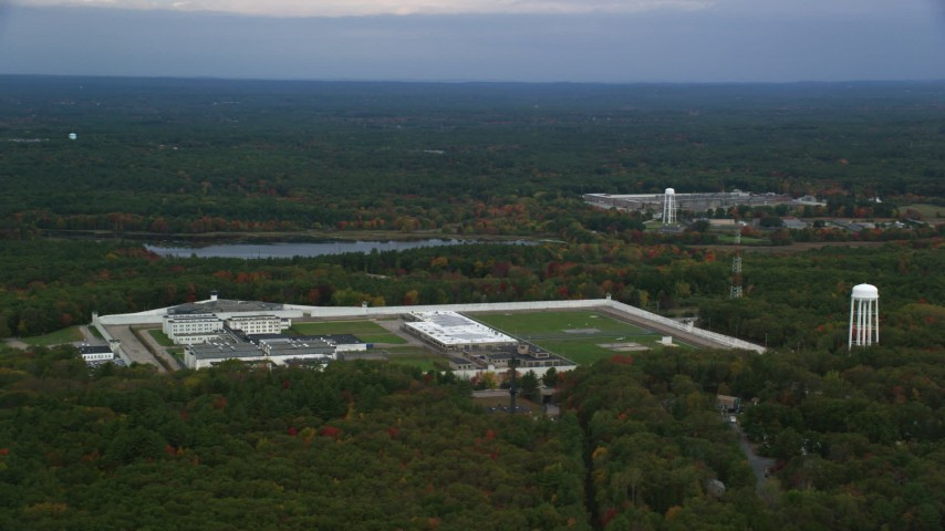 6K stock footage aerial video of a high view passing by Massachusetts Correctional Institution Cedar Junction among fall foliage, Walpole, Massachusetts Aerial Stock Footage | AX152_223