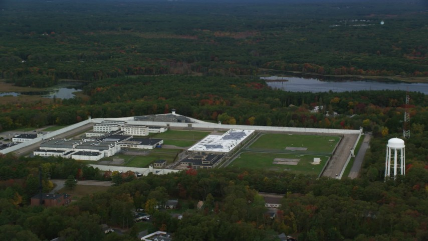 6K stock footage aerial video flying away from Massachusetts Correctional Institution Cedar Junction and water tower among fall trees, Walpole, Massachusetts Aerial Stock Footage | AX152_224