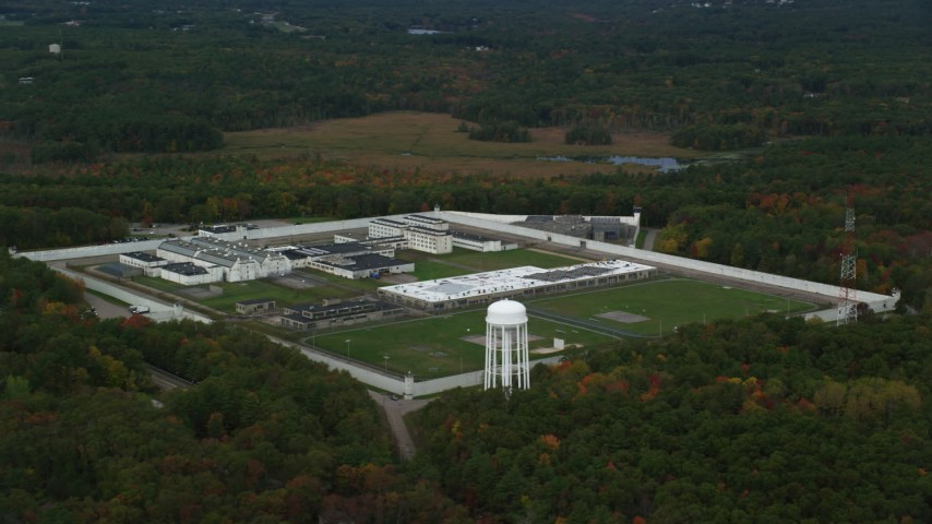 6K stock footage aerial video of a side view of Massachusetts Correctional Institution Cedar Junction surrounded by partial fall foliage, Walpole, Massachusetts Aerial Stock Footage | AX152_225