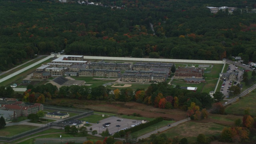 6K stock footage aerial video of a high approach toward Massachusetts Correctional Institution at Norfolk, and fall foliage, Massachusetts Aerial Stock Footage | AX152_226