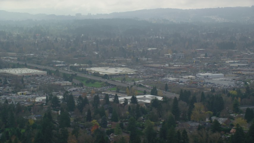 6K aerial video flying by shopping centers on a cloudy day, autumn, Beaverton, Oregon Aerial Stock Footage | AX153_005